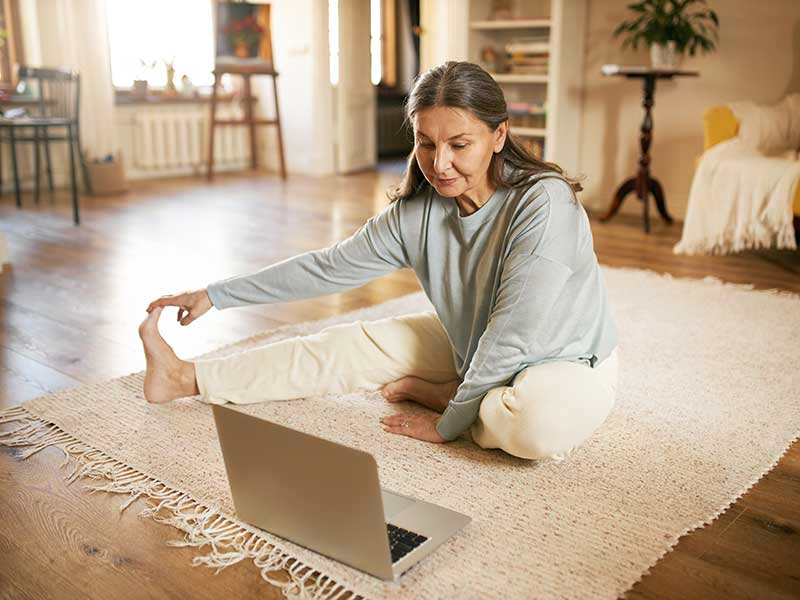 Older woman exercising in front of laptop